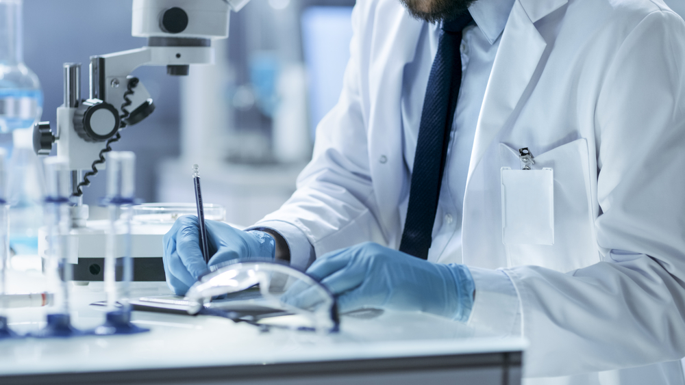 Research Scientist Writes Down Experiment Observations. He's Working in Modern Laboratory.