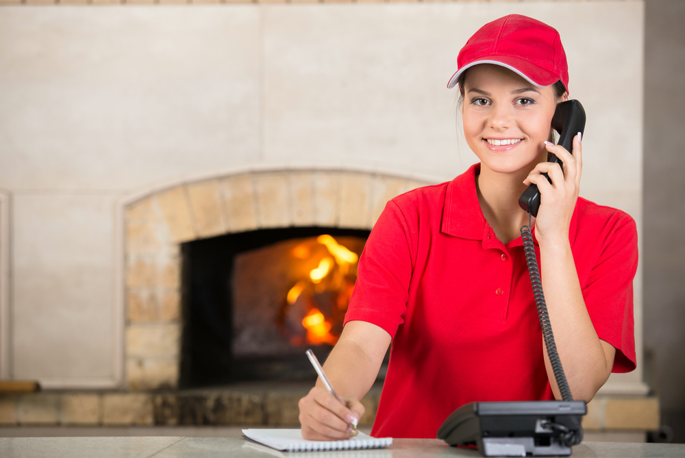 Portrait of happy delivery woman of pizza holding pen and diary for placing order by phone.