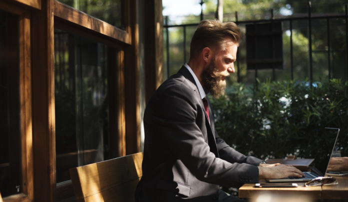 man with beard in a formal suit using a laptop