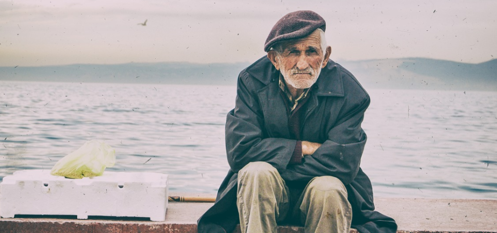 old man sitting by the sea wall