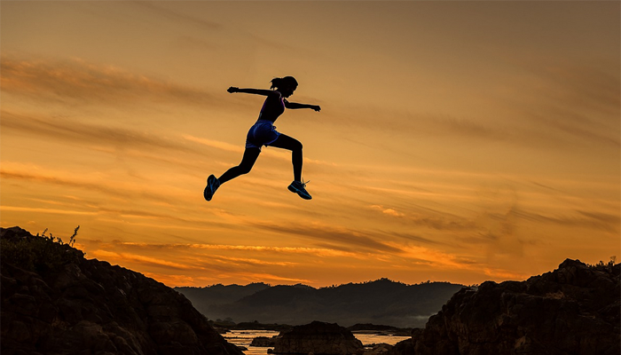 woman jumping high from a hill