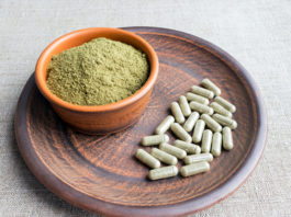 Supplement kratom green capsules and powder on brown plate. Herbal product alt-medicine kratom is opioid. Home alternative pain remedy, opioid addiction, dangerous painkiller, overdose. Close up
